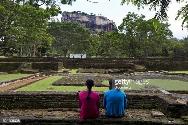 Visitors sit in front of the 'Lion Rock' in the gardens of the Ancient City of Sigiriya near Dambulla Central province Sri Lanka on Tuesday Jan 5...