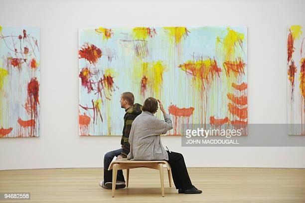 Visitors sit in front of US artist Cy Twombly's 'Lepanto' series at the Brandhorst museum in Munich December 15 2009 The Brandhorst Museum was opened...