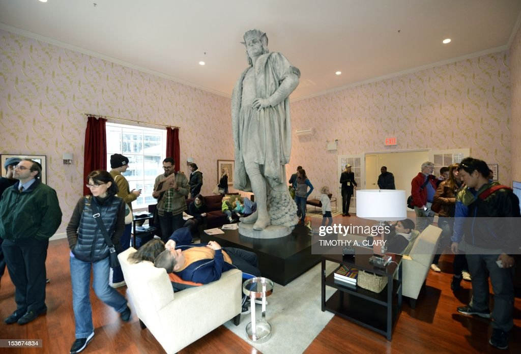 Visitors sit in Japanese artist Tatsu Nishi's installation around the colossal 13-foot-tall statue of Christopher Columbus at Columbus Circle in New York on October 8, 2012 standing in a fully furnished, modern living room featuring tables, chairs, couch, rug, and flat-screen television, reflecting the artist's interpretation of contemporary New York style. His installation around the weathered marble statue, designed by the Italian sculptor Gaetano Russo in 1892, rises to more than 75 feet atop a granite column. Visitors can enter the 'Discovering Columbus' apartment built around the statue elevated from the ground by scaffolding, located in the downtown Columbus Circle until November 18.