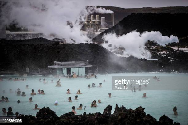 Visitors sit in the geothermal waters at the Blue Lagoon close to the Icelandic capital of Reykjavik on August 30 2018 in Reykjavik Iceland