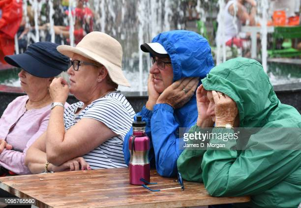 Visitors sit in the rain watching the tennis action on big TV screens2 during day five of the 2019 Australian Open at Melbourne Park on January 18,...