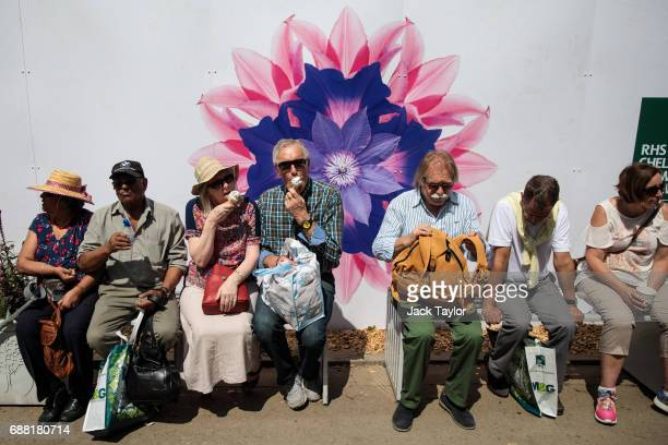 Visitors sit in the sunshine eating ice creams at the Chelsea Flower Show on May 25 2017 in London England Visitors are enjoying warm weather and...