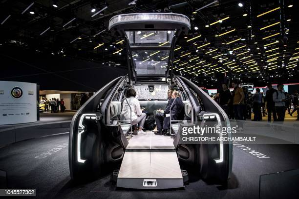 Visitors sit inside a Renault EZGO autonomous electric concept car presented during the Paris Motor Show on October 4 2018 in Paris