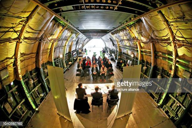 Visitors sit inside an Antonov AN124 the world's largest freight plane photographed during a press conference held in the plane during the Intec and...