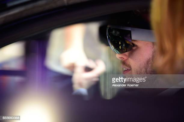 Visitors sit inside an electrical BMW i8 car while wearing a Virtual Reality glasses at the Intel stand at the CeBIT 2017 Technology Trade Fair on...