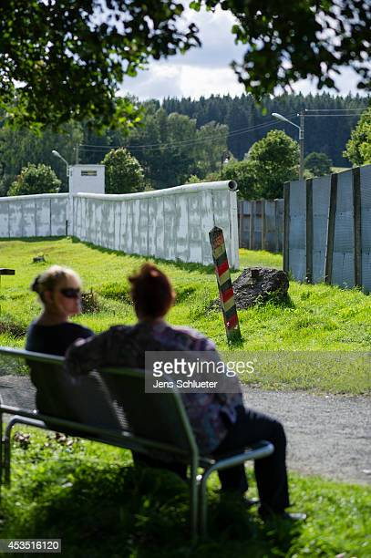 Visitors sit near border and security installations of a stillstanding section of the wall that once divided East and West Germany during the Cold...