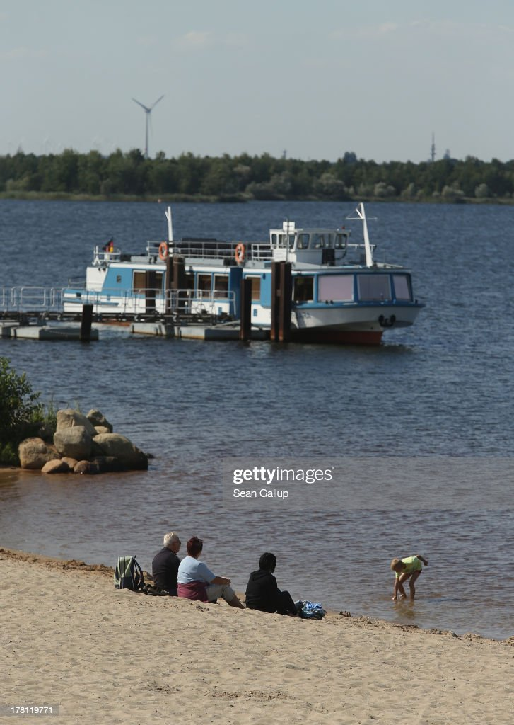 Visitors sit on a beach next to a passenger ship on the shore of artificial Senftenberger See lake on August 26, 2013 in Grosskoschen, Germany. Senftenberger See was once an open-pit lignite coal mine flooded after it shuttered in the late 1960s, and today it is popular among tourists, wind surfers and fishermen. In a development project initiated by state government, other nearby former open-pit mines that once evoked a lunar landscape are being turned into lakes in a long-term rejuvenation effort that is also intended to make the area a viable tourist destination. Mineral residue in the mines, however, is proving a difficult stumbling block that is making many of the new lakes too acidic to sustain marine life in the short term.