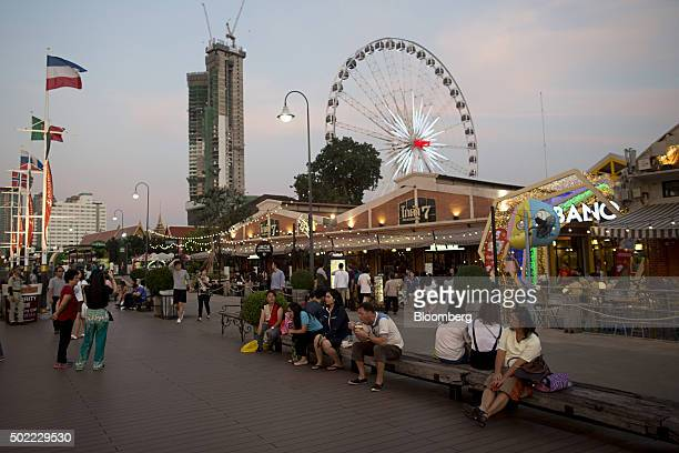 Visitors sit on a bench in front of restaurants as a ferris wheel operates in the background at Asiatique The Riverfront openair mall in Bangkok...