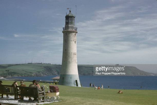 Visitors sit on benches in front of Smeaton's Tower at Plymouth Hoe with the Mount Batten peninsula, Batten Bay and Plymouth Sound beyond, in Devon,...