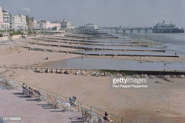 Visitors sit on deckchairs by groynes on the sand and shingle beach by the seafront at the seaside resort of Eastbourne in East Sussex on the south...