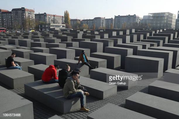 Visitors sit on stellae at the Monument to the Murdered Jews of Europe also called the Holocaust Memorial prior to the 80th anniversary of the...