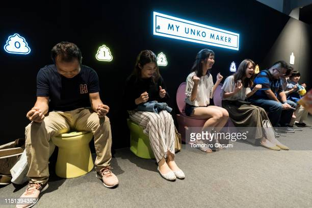 Visitors sit on toilet bowls at the Unko Museum Yokohama on May 24 2019 in Yokohama Japan The temporary popup museum lets visitors learn about poop...