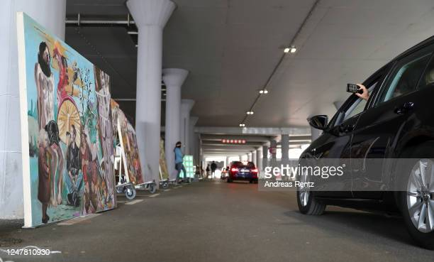 Visitors sitting in their cars drive through at the Nachtbroetchen 20 drivein PopupExhibition during the Coronavirus crisis at Airport Cologne Bonn...