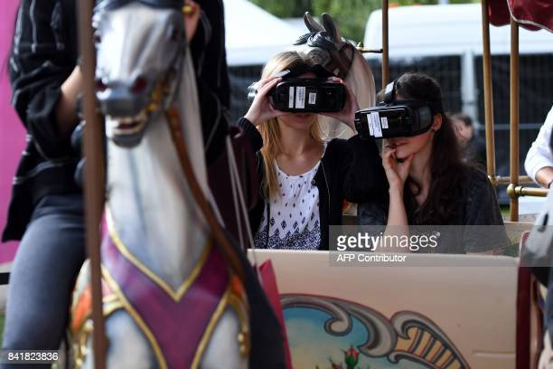 Visitors sitting on a carousel try out virtual glasses at the booth of Deutsche Telekom at the IFA Consumer Electronics Fair in Berlin on September 2...
