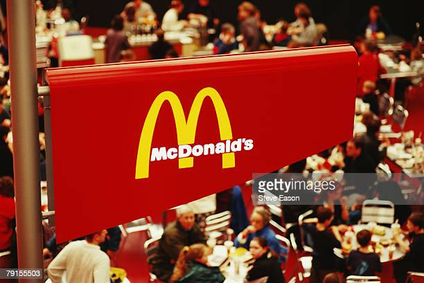 Visitors sitting underneath a sign for McDonalds inside the Millenium Dome, designed by Richard Rogers, Greenwich, 13th February 2000.
