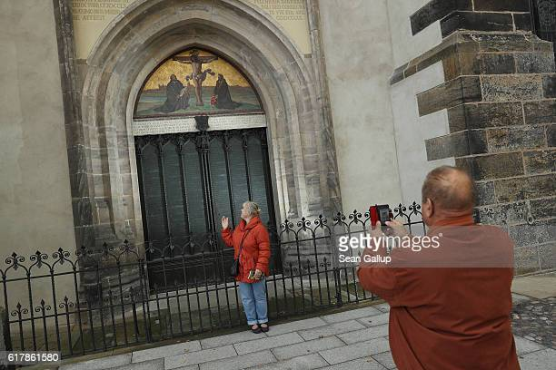 Visitors snap photos of one another in front of the cast metal reproduction of Martin Luther's 95 theses in the doorway where in 1517 Luther...