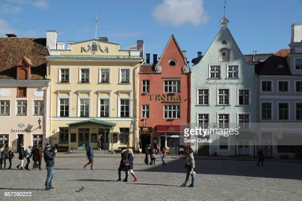 Visitors snap photos of one another on Town Hall Square in the historic city center on March 24 2017 in Tallinn Estonia Tallinn's old town escaped...