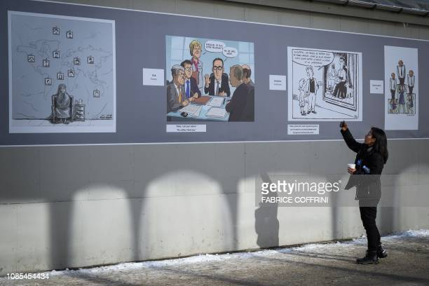 A visitors snaps a picture of a cartoon exhibition at the Davos Congress Centre ahead of the opening of the 2019 World Economic Forum annual meeting...