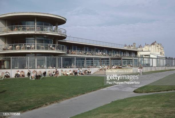 Visitors, some seated in deckchairs, enjoy an afternoon concert in the grounds of the De La Warr Pavilion on the seafront at Bexhill on Sea in East...