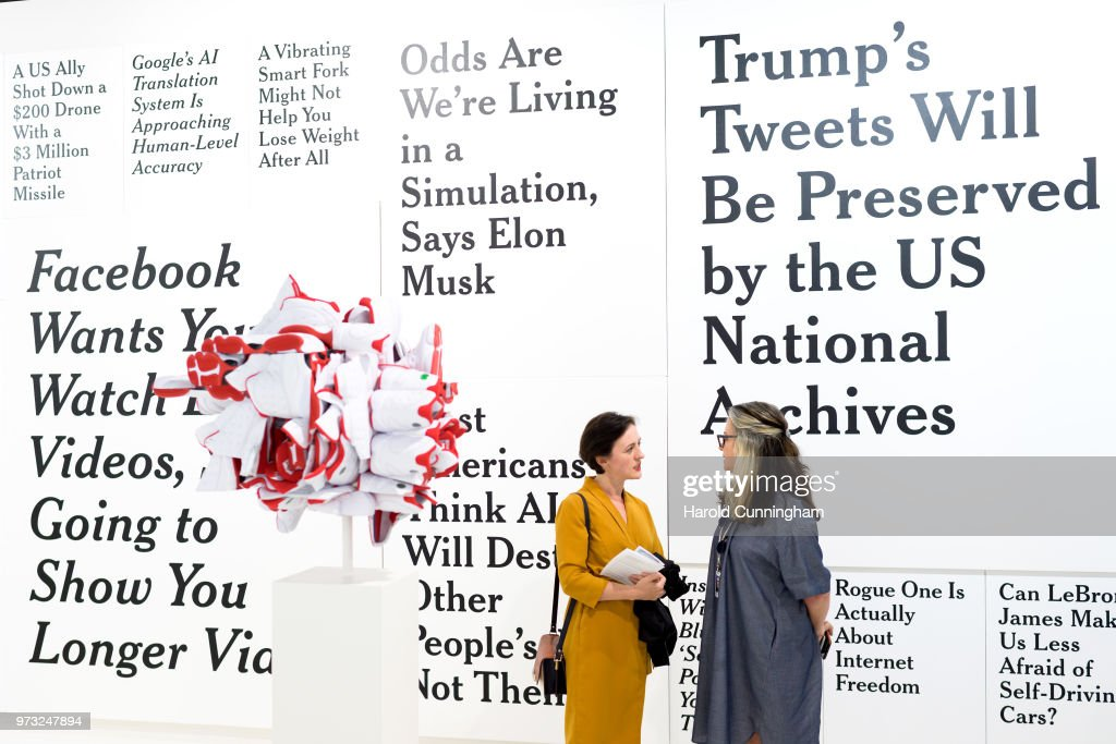Visitors speak in front of the artwork of Ron Terada 'TL; DR1' during the press preview for Art Basel at Basel Messe on June 13, 2018 in Basel, Switzerland. Art Basel is one of the most prestigious art fair in the world showcasing the work of more than 4,000 artists selected by 300 leading art galleries.