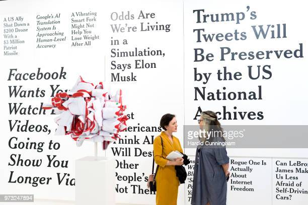 Visitors speak in front of the artwork of Ron Terada 'TL DR1' during the press preview for Art Basel at Basel Messe on June 13 2018 in Basel...