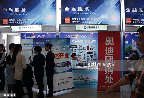 Visitors speak to staff members at China Construction Bank Corp's booth for auto loans at the Wuhan Motor Show 2013 in Wuhan China on Saturday Oct 19...