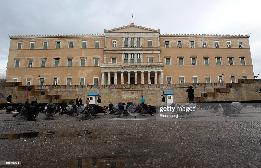Visitors stand and take photographs in front of the Greek parliament building on Syntagma Square in Athens, Greece, on Sunday, Feb. 12, 2012. Greek Prime Minister Lucas Papademos won parliamentary approval for austerity measures to secure an international bailout after rioters protesting the measures battled police and set fire to buildings in downtown Athens. Photographer: Simon Dawson/Bloomberg via Getty Images