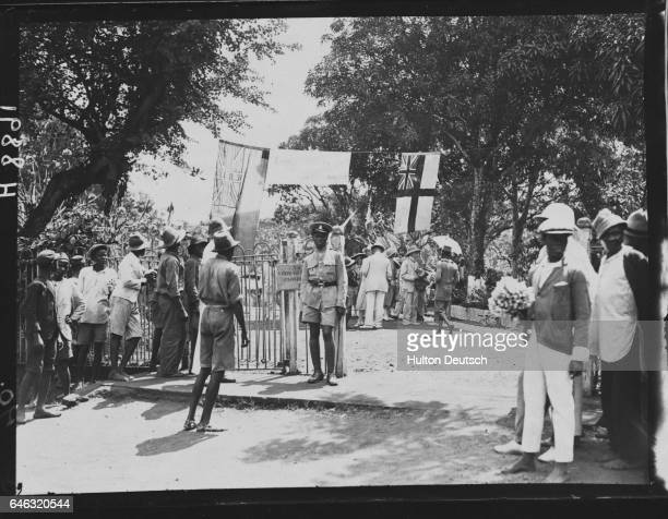Visitors stand around the entrance to the Botanical gardens in Freetown Sierra Leone
