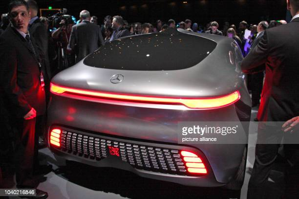 Visitors stand around the F015 selfdriving concept car of car manufacturer Daimler on display at the 2015 International Consumer Electronics Show in...