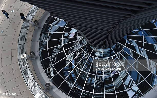 Visitors stand at the ground in the glass cupola of the Reichstag building that hosts the German parliament in Berlin Germany on June 10 2016 / AFP /...
