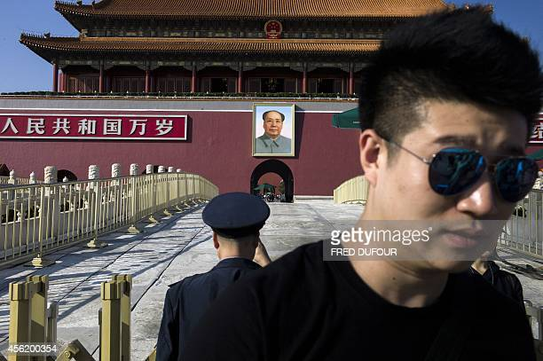 Visitors stand before a portrait of Mao Zedong at Tiananmen Gate and the Forbidden City in Beijing on September 27 2014 China will celebrate its...