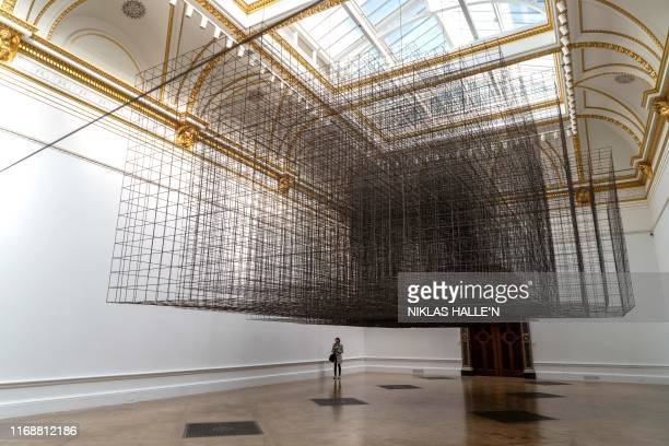 Visitors stand beneath an art installation entitled 'Matrix' during a presspreview at The Royal Academy of Arts in London on September 17 for the...