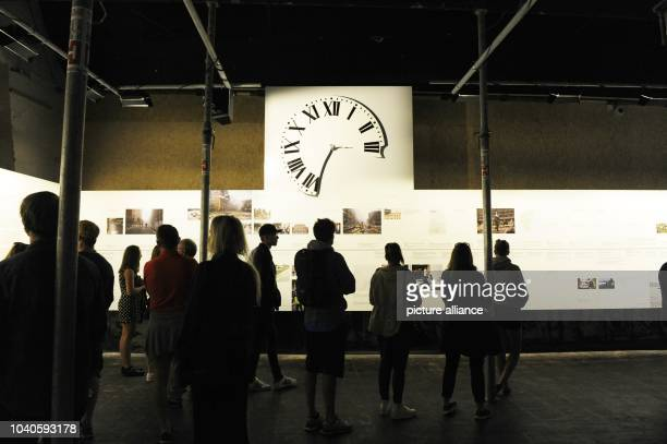 Visitors stand in front of a 17metre timeline of events of the 22 July 2011 in the '22 July Centre' in Oslo Norway 30 July 2015 The damaged clock...