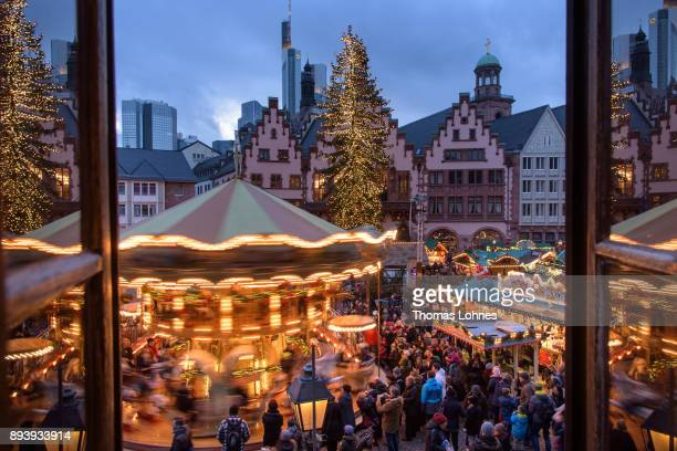 Visitors stand in front of a carousel walk among stalls selling mulled wine pastries sausages Christmas decorations handicrafts and other Christmas...