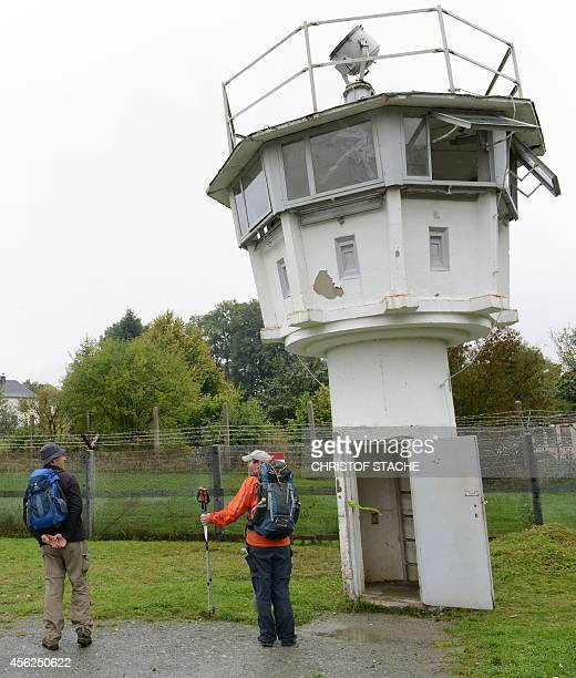 Visitors stand in front of a former watch tower of German Democratic Republic at the DeutschDeutsche Museum in the former border location of...