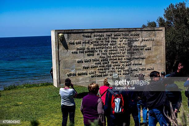 Visitors stand in front of a memorial the day before the upcoming Dawn Service commemoration ceremony to honour Australian and New Zealand soldiers...