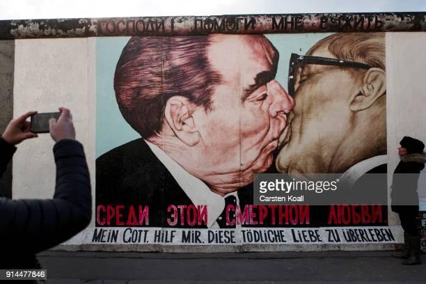 Visitors stand in front of a mural depicting former Soviet leader Leonid Brezhnev kissing former communist East German leader Erich Honecker at the...
