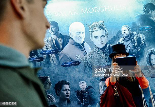 Visitors stand in front of a poster with characters from the HBO American fantasy drama television series Game of Thrones at the International Game...