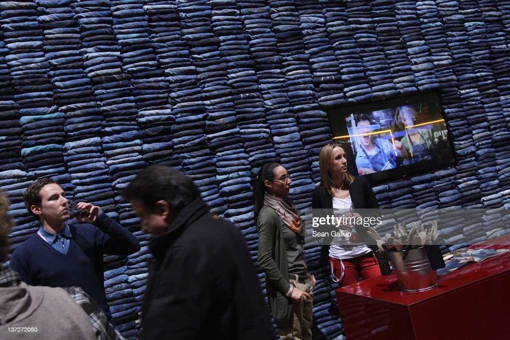 Visitors stand in front of a wall made of denim jeans at the Mavi stand at the 2012 Winter Bread And Butter fashion trade fair at former Tempelhof Airport on January 18, 2012 in Berlin, Germany. Bread And Butter is a semi-annual event and is among Europe's major fashion trade fairs.