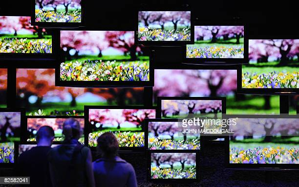 Visitors stand in front of a wall of plasma screens at the Panasonic stand at the IFA Consumer Electronics Trade Fair at Berlin's fair ground August...
