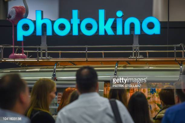 Visitors stand in front of an advertising at the Photokina trade fair in Cologne western Germany on September 27 2018 The fair for the photographic...