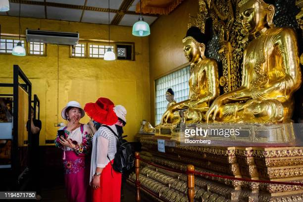 Visitors stand in front of gold Buddha statues at Shwedagon Pagoda in Yangon, Mayanmar, on Saturday, Jan. 18, 2020. China and neighboring Myanmar...