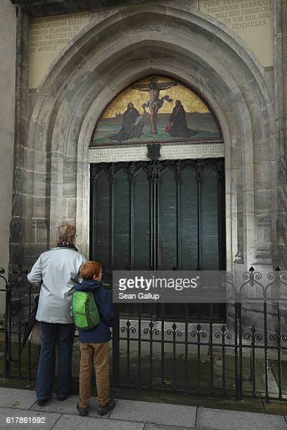 Visitors stand in front of the cast metal reproduction of Martin Luther's 95 theses in the doorway where in 1517 Luther originally nailed his theses...