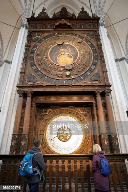 Visitors stand in front of the new calendar disc at the astronomical clock in the Marien church in Rostock Germany 28 December 2017 The monumental...