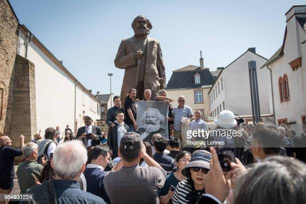 Visitors stand in front of the sculpture of German philosopher and revolutionary Karl Marx after the inauguration at the 200th anniversary of the...