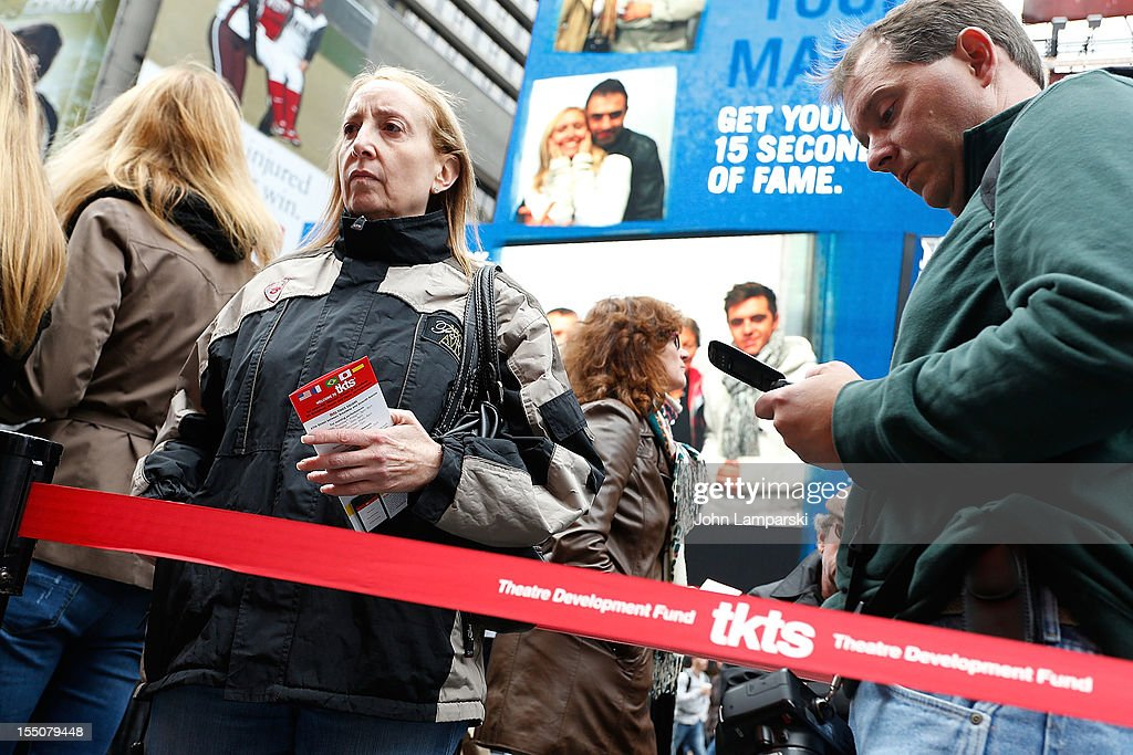 Visitors stand in line to purchase tickets to Broadway Shows in Times Square following Hurricane Sandy on October 31, 2012 in New York City.