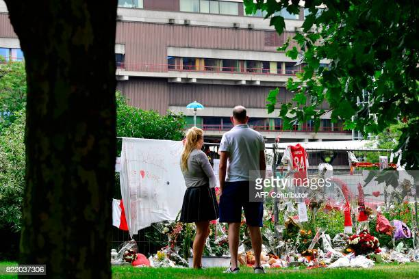 Visitors stand in silence next to items placed by the hospital where the Ajax midfielder Abdelhak Nouri receives treatments in Amsterdam on July 22...