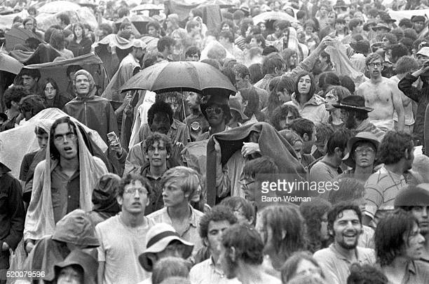 Visitors stand in the rain at the Woodstock Music Art Fair Bethel NY August 15 1969