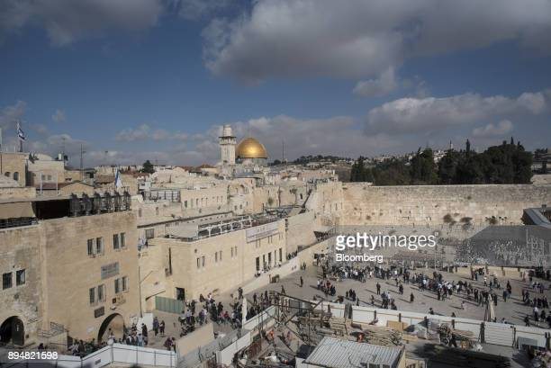Visitors stand in the square beside the Western Wall with the Dome of the Rock visible on the skyline beyond in the Old City in Jerusalem Israel on...