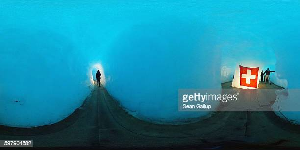 Visitors stand inside an icecavern room with a Swiss flag that lies at the end of a 100meterlong tunnel hewn into the Rhone glacier as a tourist...